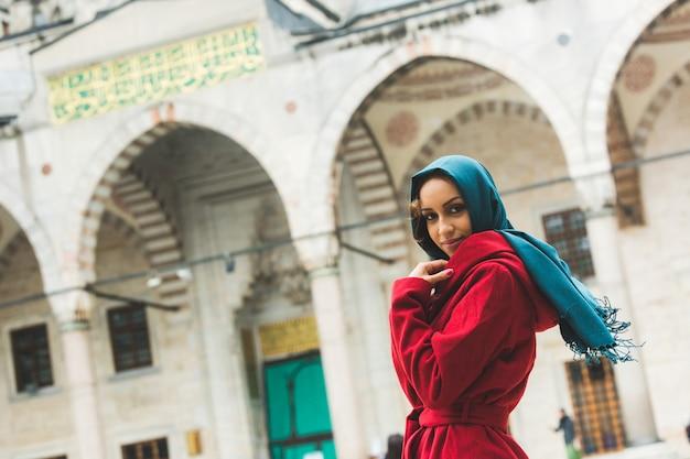 Jovem mulher árabe vestindo véu na frente de uma mesquita Foto Premium
