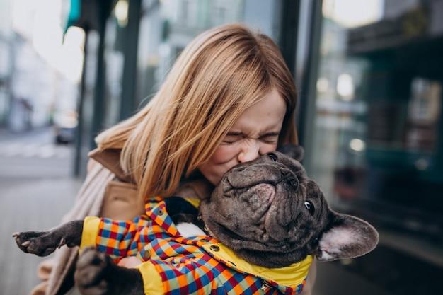 Jovem mulher às compras com seu cachorro bulldog francês Foto gratuita