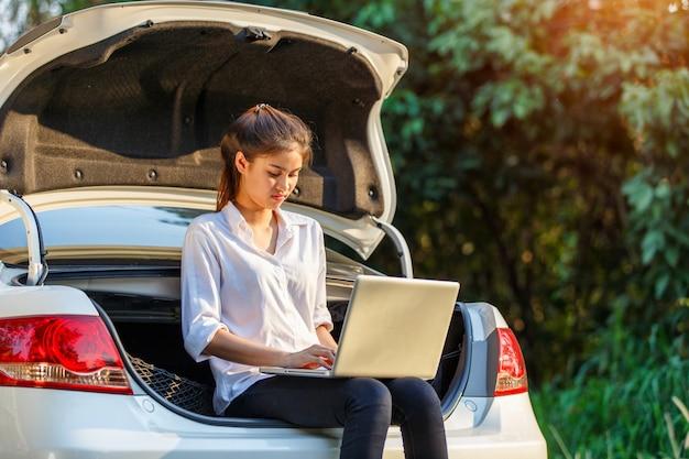 Jovem, mulher asian, sentando, ligado, hatchback, car, com, caderno Foto Premium