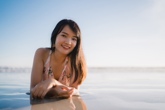 Jovem, mulher asian, sentimento, feliz, ligado, praia, bonito, femininas, feliz, relaxe, sorrindo, divertimento, ligado, praia Foto gratuita