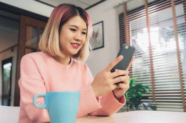 Jovem, mulher asian, usando, smartphone, enquanto, mentindo, escrivaninha, em, dela, sala de estar Foto gratuita