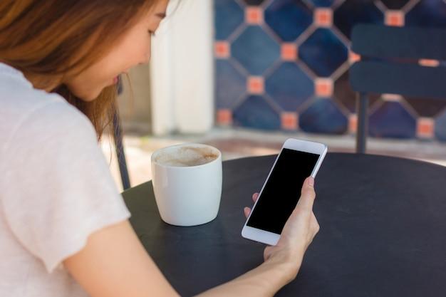 Jovem, mulher asian, usando, smartphone, zombe cima, em branco, tela preta, em, café Foto gratuita