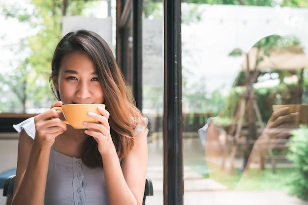 Jovem mulher asiática alegre que bebe o café ou o chá morno que aprecia a ao sentar-se no café Foto gratuita