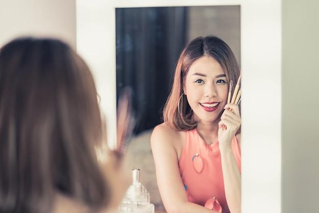 Jovem mulher asiática bonita fazendo maquiagem perto de espelho Foto Premium