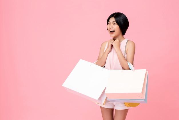 Jovem mulher asiática carregando sacolas de compras em gesto surpreso e animado Foto Premium