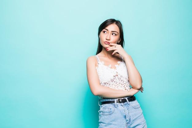 Jovem mulher asiática com as mãos perto do rosto, isolado na parede verde Foto gratuita
