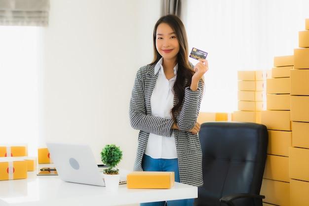 Jovem mulher asiática com cartão de crédito e caixa de papelão Foto gratuita