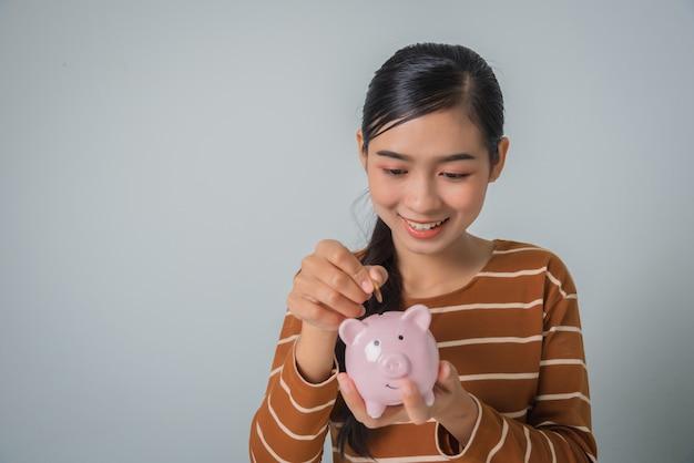 Jovem mulher asiática com dinheiro moeda e cofrinho Foto Premium