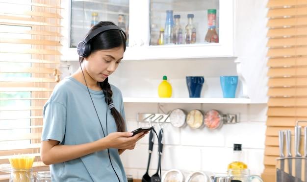 Jovem mulher asiática com fones de ouvido, ouvindo música do telefone móvel em casa cozinha Foto Premium