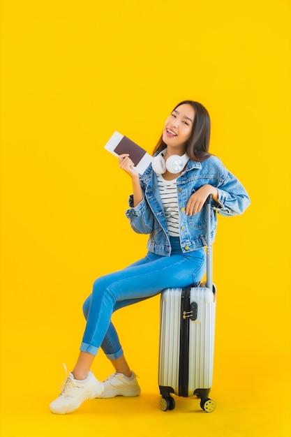 Jovem mulher asiática com mala e passaporte Foto gratuita