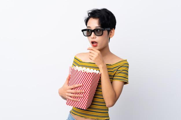 Jovem mulher asiática com óculos 3d e segurando um grande balde de pipocas enquanto olha de lado Foto Premium