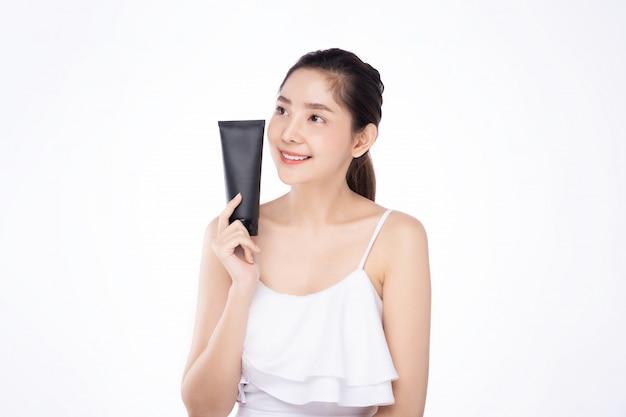 Jovem mulher asiática com pele branca fresca limpa, segurando o creme de tratamento facial Foto Premium