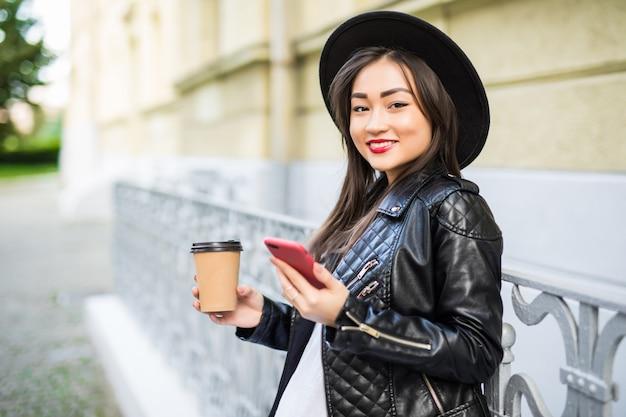 Jovem mulher asiática com smartphone em pé contra a rua com telefone e xícara de café Foto gratuita