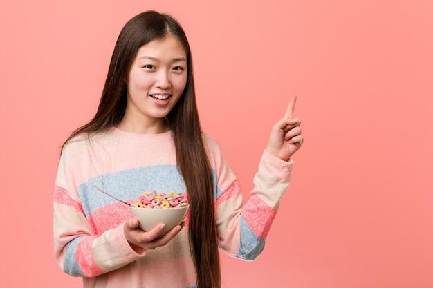Jovem mulher asiática com uma tigela de cereais, sorrindo alegremente apontando com o dedo indicador fora. Foto Premium