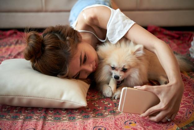 Jovem mulher asiática, deitado no chão com pequeno cão de estimação e tirar selfies com smartphone Foto gratuita