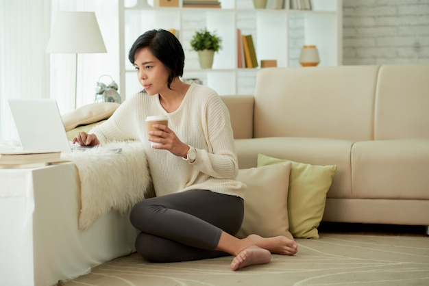 Jovem mulher asiática, desfrutando de confortos em casa Foto gratuita