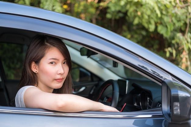 Jovem mulher asiática dirigindo um carro Foto Premium