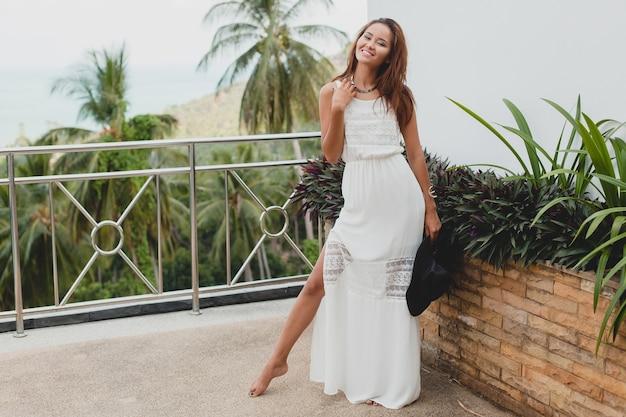 Jovem mulher asiática elegante com vestido boho branco, estilo vintage, natural, sorridente, feliz, férias tropicais, hotel, fundo de palmeiras Foto gratuita