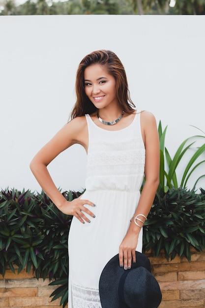 Jovem mulher asiática elegante em um vestido boho branco, estilo vintage, natural, sorridente, feliz, férias tropicais, hotel, lua de mel Foto gratuita