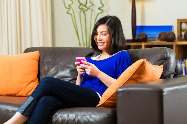 Jovem mulher asiática em casa no sofá Foto Premium