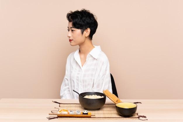 Jovem mulher asiática em uma mesa com tigela de macarrão e sushi, olhando de lado Foto Premium