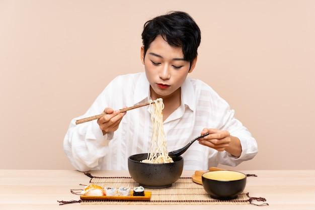 Jovem mulher asiática em uma mesa com uma tigela de macarrão e sushi Foto Premium