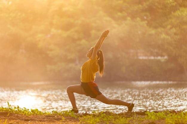 Jovem, mulher asiática, prática, guerreira yoga, pose, perto, lago, em, pôr do sol, tempo Foto Premium