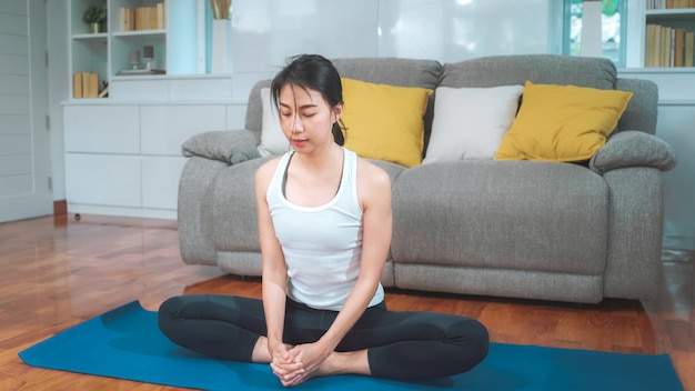 Jovem mulher asiática praticando ioga na sala de estar. mulher bonita atraente malhando para saudável em casa. conceito de estilo de vida mulher exercício. Foto gratuita