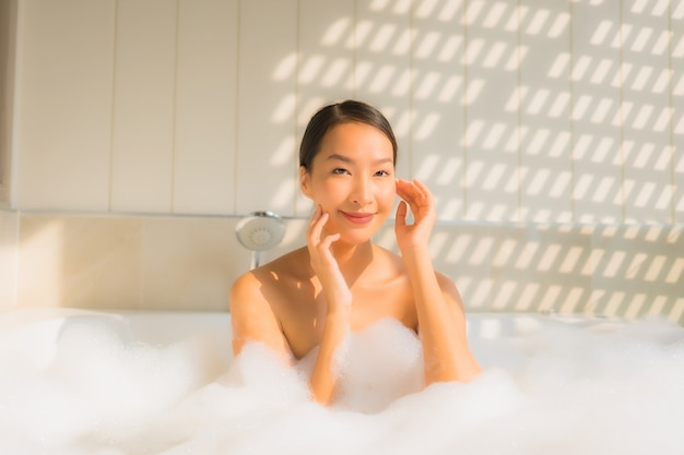 Jovem mulher asiática retrato relaxar tomar um banho na banheira Foto gratuita