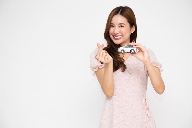 Jovem mulher asiática segurando o modelo do carro e mostrando um pequeno sinal de coração isolado no fundo branco Foto Premium