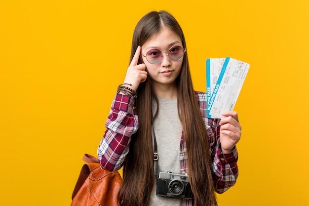 Jovem mulher asiática segurando passagens aéreas apontando seu templo com o dedo, pensando, focado em uma tarefa. Foto Premium