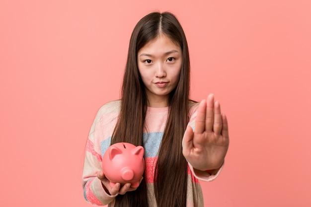 Jovem mulher asiática segurando um cofrinho em pé com a mão estendida, mostrando o sinal de stop, impedindo-o. Foto Premium