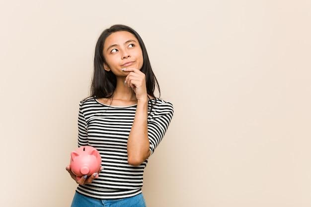 Jovem mulher asiática segurando um cofrinho, olhando de soslaio com expressão duvidosa e cética. Foto Premium