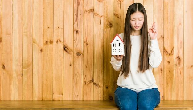 Jovem mulher asiática segurando um ícone de casa cruzando os dedos por ter sorte Foto Premium