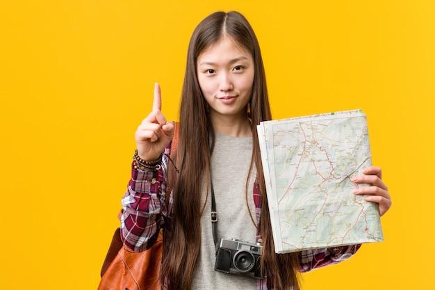 Jovem mulher asiática segurando um mapa mostrando o número um com o dedo. Foto Premium