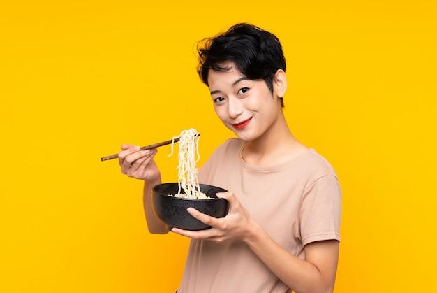 Jovem mulher asiática sobre parede amarela isolada, segurando uma tigela de macarrão com pauzinhos Foto Premium