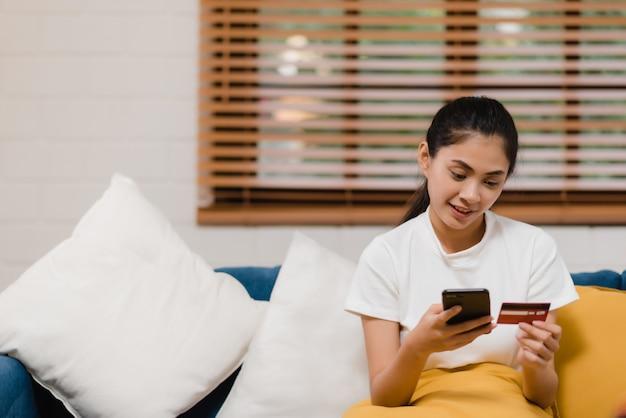 Jovem mulher asiática sorridente usando smartphone comprando compras on-line Foto gratuita