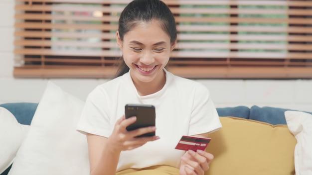 Jovem mulher asiática sorridente usando smartphone comprar compras on-line por cartão de crédito Foto gratuita