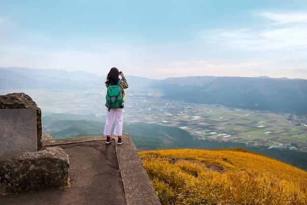 Jovem mulher asiática tirando uma foto no topo de uma montanha com bela vista Foto Premium