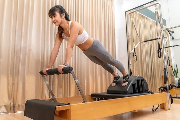 Jovem mulher asiática trabalhando em uma máquina reformadora de pilates durante seu treinamento de exercícios de saúde Foto Premium
