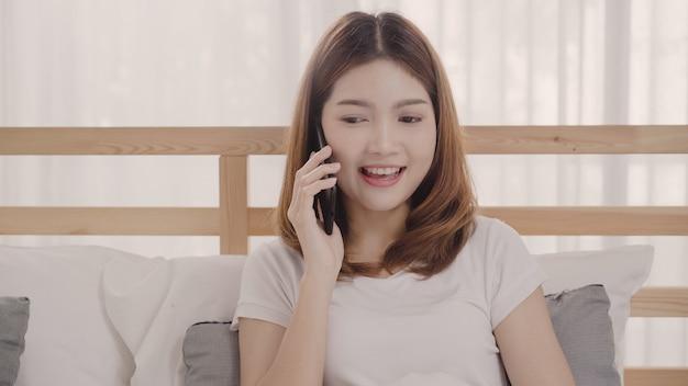 Jovem mulher asiática usando smartphone enquanto estava deitado na cama depois de acordar de manhã Foto gratuita