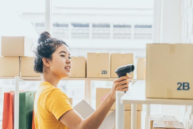 Jovem mulher asiática, verificação de mercadorias na prateleira de estoque em armazém Foto Premium