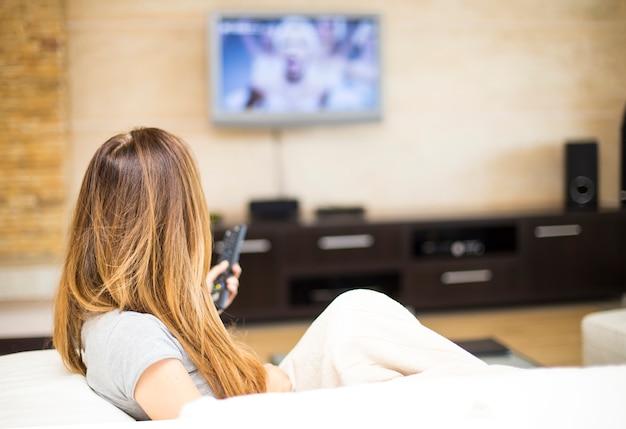 Jovem mulher assistindo tv no quarto | Foto Premium