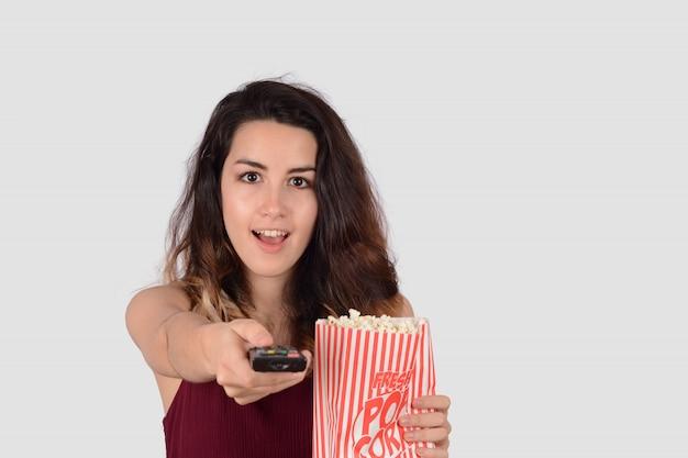 Jovem mulher assistindo um filme e comendo pipoca. Foto Premium