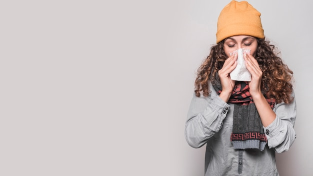 Jovem mulher assoar o nariz com lenço de papel no fundo cinza Foto gratuita