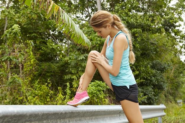Jovem mulher atlética alongamento antes de manhã correndo treino ao ar livre. Foto gratuita