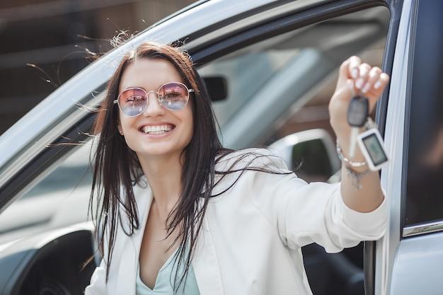 Jovem mulher atraente acabou de comprar um carro novo. feminino segurando as chaves do automóvel novo. Foto Premium