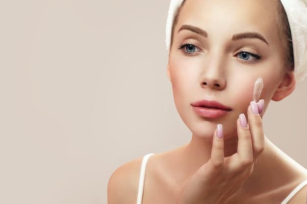 Jovem mulher atraente aplicando creme no rosto enquanto olha seu reflexo no espelho. Foto Premium