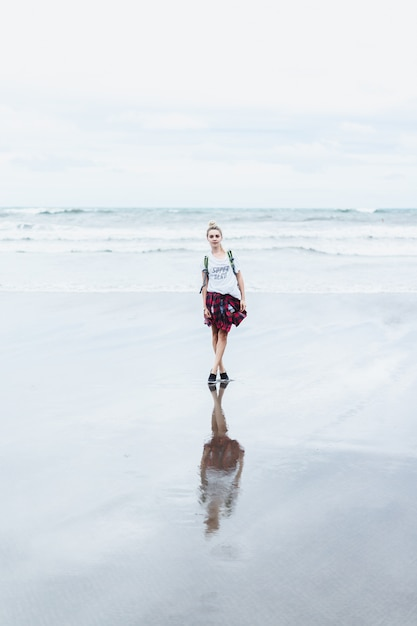 Jovem mulher atraente, caminhando ao longo da costa do oceano em uma praia arenosa Foto gratuita