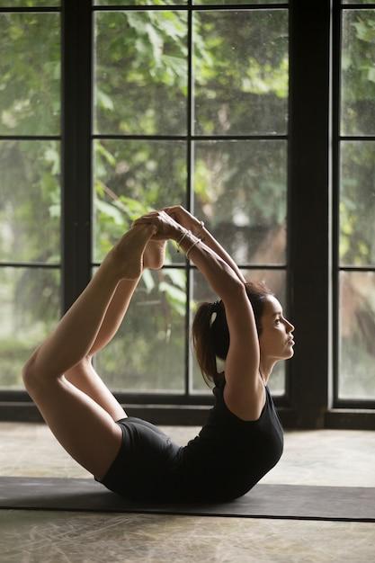 Jovem mulher atraente em dhanurasana pose, fundo de estúdio Foto gratuita